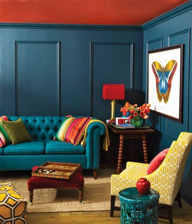 Hot turquoise Chesterfield sofa juxtaposed to a gold mid-century patterened chair, with pop color accents in tomato red, orange & avocado green. Whew.