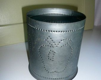 Irvins Tin Company Wall Sconce or cylinder Candle Holder with punched HEART design. These retail for over $30.00 are now discontinued. Great for displays at shows, or home decor. You could hang and use the battery operated candles or even a small floral design would be a lovely touch. These were stored a shed for a number of years, but in closed container. This one looks brand new. We did a light cleaning with damp cloth. NOTE: Candles are only shown as an example - NOT FOR SALE.  Quantity…