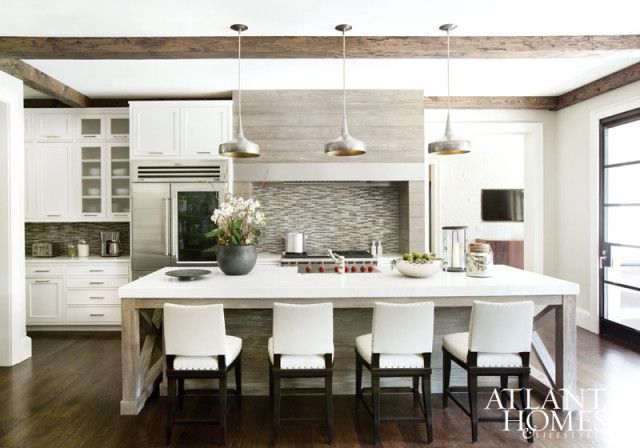 The hood, cabinetry and kitchen island were designed by Watford. Counter stools, Mattaliano. Lighting, Arteriors.