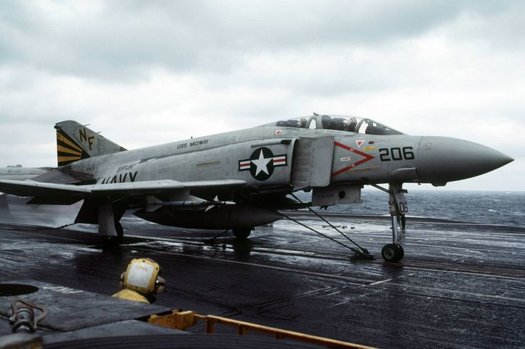 """The flight deck director, foreground, watches as a U.S. Navy McDonnell Douglas F-4S Phantom II (BuNo 153910) of Fighter Squadron VF-151 """"Vigilantes"""" is prepared for launch from a catapult aboard the aircraft carrier USS Midway (CV-41), in 1985. VF-151 was assigned to Carrier Air Wing 5 (CVW-5) aboard the Midway. Date 1 March 1985"""