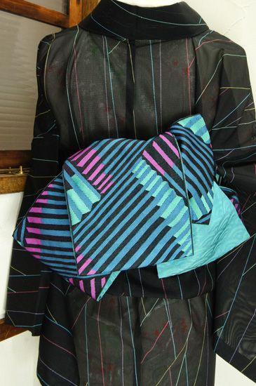 アクアブルーをベースに、ブラックとロータスピンクがアクセントになった幾何学ストライプがモダンな化繊半幅帯です。 #kimono