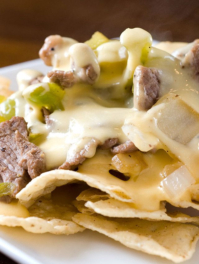 PHILLY CHEESESTEAK NACHOS~ 1 tbsp olive oil, 1 lb thinly sliced round steak, 1 tsp kosher salt, ½ tsp fresh cracked black pepper, 4 tbsp butter divided, 2 green bell peppers seeds and ribs removed diced, 1 medium yellow onion diced, 1 tbsp Worcestershire sauce, 2 tbsp flour, 1¼ cup milk, ½ tsp seasoning salt, 4 cups shredded medium cheddar cheese, 2 oz cream cheese, tortilla chips.