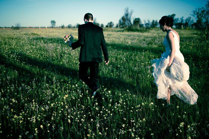 Fotografía de bodas Fotografía en color de los novios caminando por el campo durante la sesión de fotos