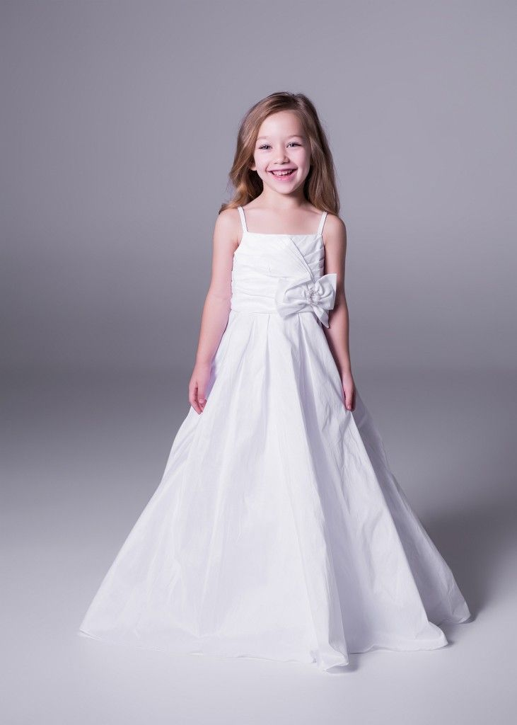 Showcase your flower girls' cuteness and let hr dream to be a bride on your big day, with this floor length flower girl dress with bow detail. Only at Bride&co stores, available in white and ivory (style FG3039). Click to Book a Free Fitting.