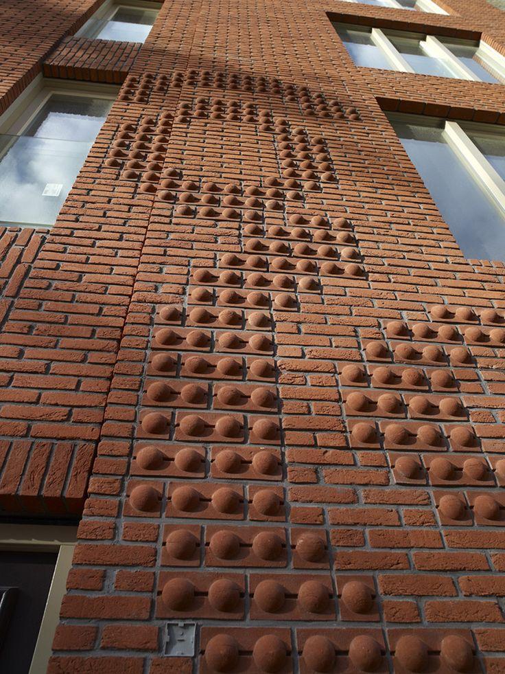 De nieuwe Crooswijk in Rotterdam, woonblokken met een sierlijk dessin.  Verrassende en sierlijke dessins, gemaakt met een speciaal voor dit project vervaardigde reliëfsteen, verfraaien de gevels.
