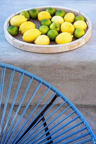 Lemons and limes on the terrace of the Superior Sea View Suite, next to a metal blue minimal chair. You can see more information at www.bohememykonos.com/superior-sea-view-suite-mykonos
