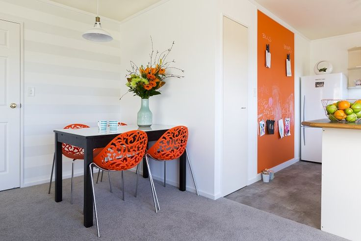 The final reveal! Subtle silver striped wallpaper hung horizontally, teams up with soft greige coloured carpet and a splash of orange chalk-board. Decorating products are available in New Zealand through Guthrie Bowron stores.