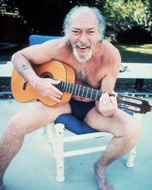 Lee Van Cleef, laughing while playing a guitar