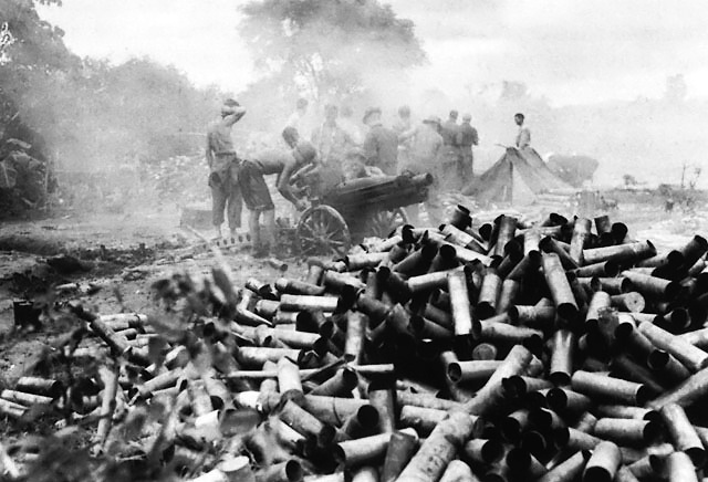 Spent 75-mm howitzer shells piling up outside the besieged city Myitkyina, Burma, mid-1944.