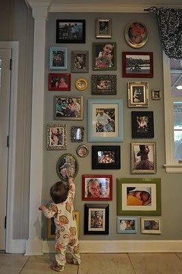 Love this photo wall - did this in my upstairs hall.  We call it the family wall because it is photos of our extended families.  I did a mix of photo frame styles but stuck to silver and black as colors.