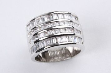 Rows of Baguettes Ring Silver: This statement cocktail piece is simple yet luxurious. A stunning ring with rows of baguettes channel set in wide band. Cubic zirconia, real rhodium electroplated over brass. $165.00