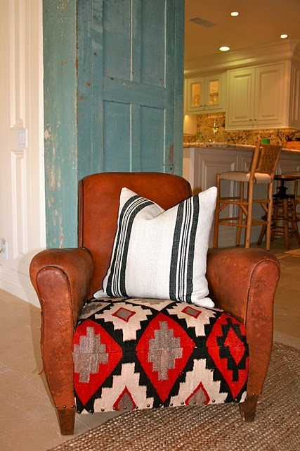 recovered old leather cushion with a navajo rug.... oh boy! And I love that it's red and black...belongs in my office!!