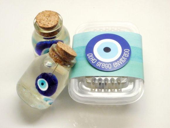 """O olho grego envidrado, é um enfeite estilo """"snow globe"""" montado em vidrinho rústico de 8cm de altura x 4cm de diâmetro fechado com rolha, contendo um olho grego grande """"pendurado"""", 3 olhos gregos pequenos e paetês em meio gelatinoso, o que confere ar bucólico à peça.    Embalagem em potinho tipo tupperware descartável com cinta de papel e tag.        QUANTIDADE MÍNIMA PARA ENCOMENDA Produto vendido por unidade (não há quantidade mínima para encomenda). Preços diferenciados para compras ..."""