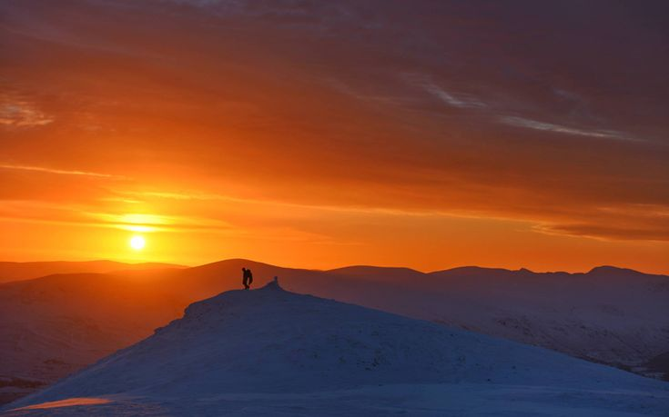 The sun rises over the frozen snow covered Lake District fells