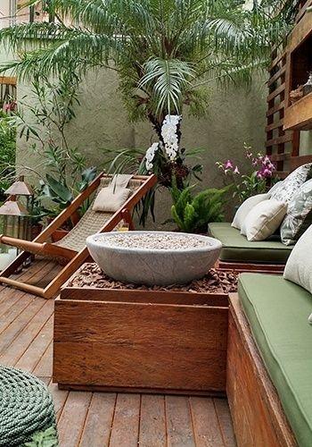 Em uma casa na zona sul de São Paulo, a paisagista Gigi Botelho dispôs sobre o deck de madeira de demolição uma área de descanso com cadeira de corda, mesa de apoio, bancos com almofadas e uma pira de pedra-sabão