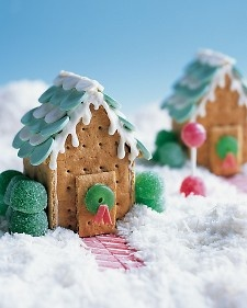 Building Cookie Cottages: Candy Land - Construct a basic cottage, and add details such as a wafer-candy roof and icicles made of royal icing. The wreaths are gummy rings with chewing-gum ribbons cut with scissors. The landscaping includes striped-gum paths, gumdrop shrubs, and a lollipop topiary. The snow is a mix of shredded and desiccated coconut. #Christmas #Holidays