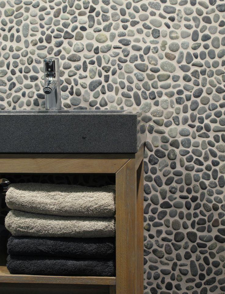 Kiezel mozaïek aan wand in badkamer