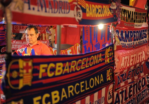 A stall owner sells Atletico Madrid and Barcelona merchandise before the Spanish Super Cup first leg match between Atletico de Madrid and Barcelona at Vicente Calderon Stadium on August 21, 2013 in Madrid, Spain.