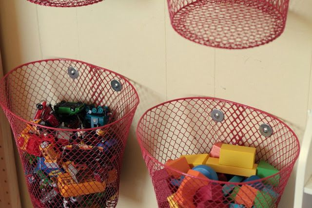 Hang dollar store trash cans on the wall to store toys