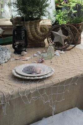 Nautical tablescape with decorative fishnet: http://www.completely-coastal.com/2012/11/top-tablescape-idea-nautical.html