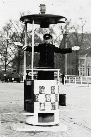 Verkeersagent Jan W. Vernooij, het verkeer regelend vanaf een verhoging op de Smakkelaarsbrug over de Stadsbuitengracht te Utrecht.  Jan Vernooij was één van de zes initiatiefnemers die, na het herderlijk schrijven van de Nederlandse bisschoppen, bij politie-president Kerlen zijn standpunt meedeelde en weigerde om nog langer joden en jongeren voor de Arbeidsinzet op te halen en vervolgens moest onderduiken.
