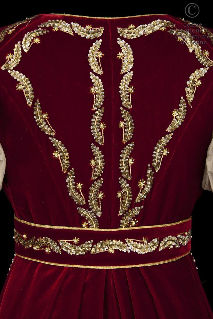 Diana  Descriptif costume:  Costume de style empire. Robe à taille haute en moire rose pâle, manches ballons avec rangs de perles et broderies dans le bas de la robe. Manteau de cour avec traîne en velours rouge brodé or.