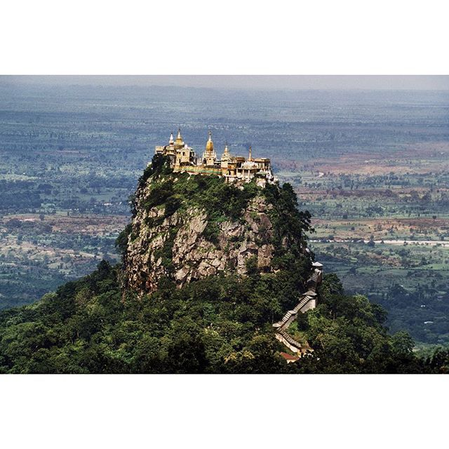 Photo by Steve McCurry. The stairway is narrow and steep as it climbs a 300-foot lava plug crowned by Buddhist temples. The plug rises from the slope of Mount Popa an extinct volcano, where thousands of pilgrims flock each May to a festival honoring a multitude of terrestial spirits called nats. Burma's Buddhists have a healthy respect for the nats, who bestow favors on those who honor them and inflict punishment on non-believers.