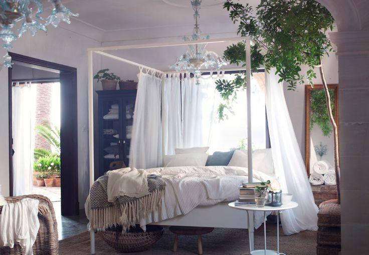 Un tocco moderno su un letto a baldacchino bianco circondato da tende bianche e piante verdi, sotto un lampadario importante - IKEA