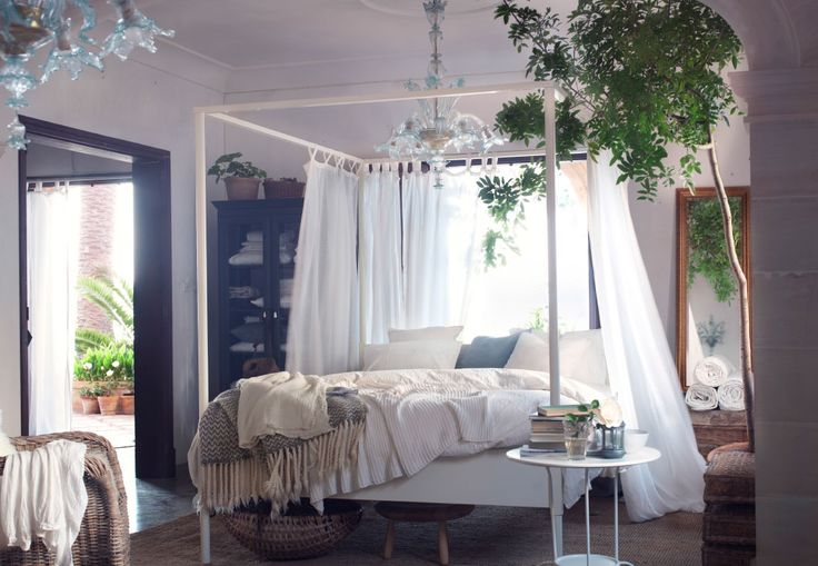 A modern take on a four poster bed with a white bed surrounded by white curtains, green plants and underneath a chandelier