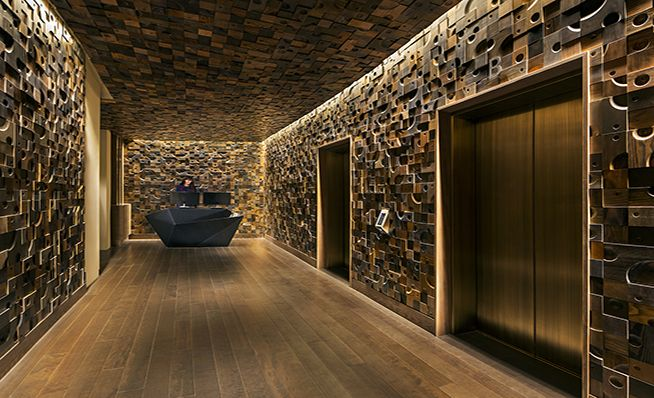 Nobu Hotel Suites Las Vegas Custom wood blocks made from fir, hemlock, and oak line the lobby walls in random and irregular shapes, sizes, and colors.