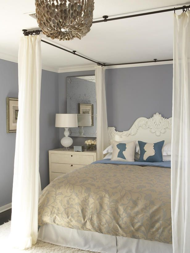 Curtain rods suspended from the ceiling provide support for the linen bed