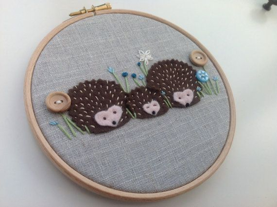 A cute fabric picture of three hedgehogs framed in a 6 embroidery hoop  This hedgehog family are made from brown felt that has been hand sewn onto