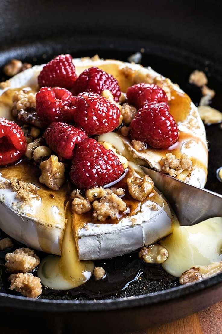 Raspberry and Walnut Baked Brie! Warm baked brie topped with brown sugar, candied walnuts, and raspberries soaked in a honey balsamic sauce. | HomemadeHooplah.com