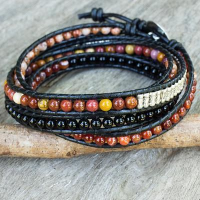 Jupiter Rising   Spotted and swirled with color, like mysterious Jupiter, ruddy carnelian and jasper globes align in this wrap bracelet from Siriporn in Thailand. They are complemented by jet-black onyx and stamped silver barrel beads of Thai hill tribe origin. The artisan knots the beads on black nylon cords and secures the bracelet with a pretty silver button..950 Silver