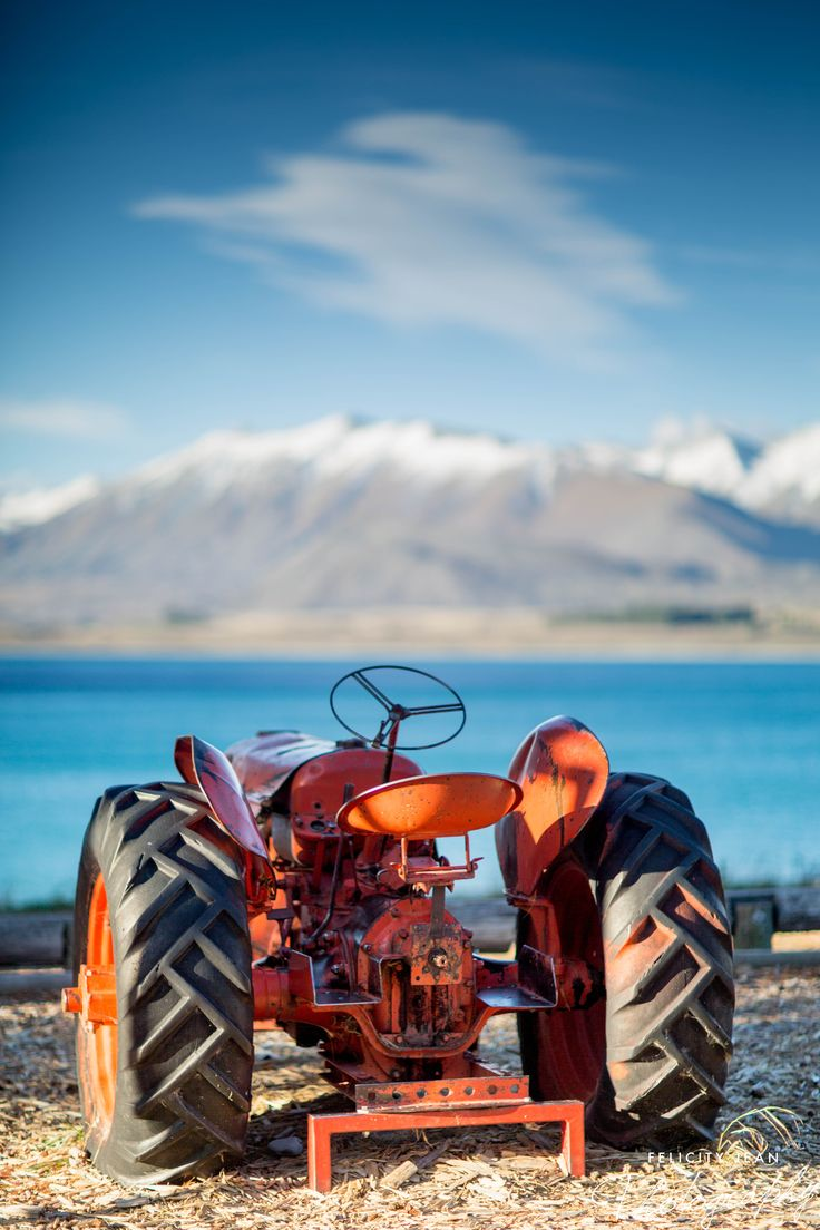 tractor at lake tekapo in winter with snow capped surrounding mountains by felicity jean photography