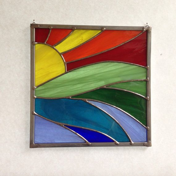This beautiful stained glass rainbow sunset suncatcher is made of hand cut glass. The pieces are individually wrapped in copper foil, and soldered. It comes ready to hang with sturdy hooks and clear line, and measures approximately 7 inches square including the zinc frame (all suncatchers are handmade and therefore vary in size slightly). The solder is waxed and buffed to shine. This suncatcher will look great in any window. Glass colors: Red, Orange, Yellow, Green, Blue.  This item is made…