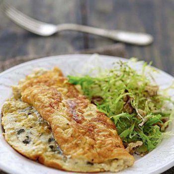 OMELETTE SOUFFLEE AU ROQUEFORT (Pour 4 P : 8 œufs - 125 g de roquefort - 50 g de cerneaux de noix - 1 cœur de salade frisée - 1 c à s de crème épaisse - 25 g de beurre - 1 échalote - 1 c à s de vinaigre balsamique - 3 c à s d'huile - sel poivre)
