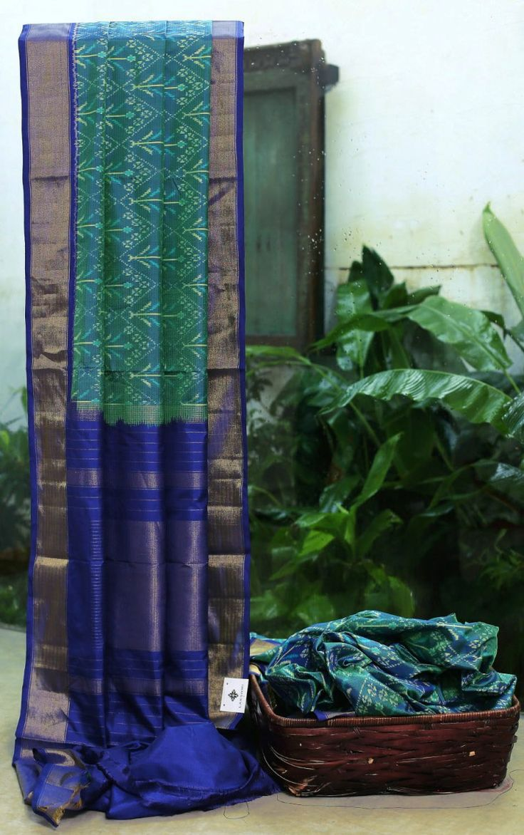 GREEN WITH BLUE SHOT IKKAT SILK IS INTRICATELY WOVEN ALL OVER. THE ROYAL BLUE WITH GOLD ZARI BORDER AND PALLU ADDS APPEAL TO THE SAREE.
