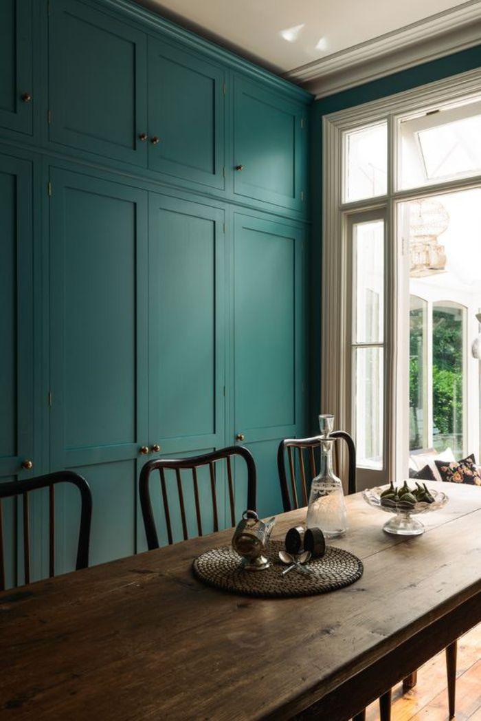 une salle à manger de style maison de campagne, ambiance naturelle et apaisante avec un mur de placards ajustés bleu paon