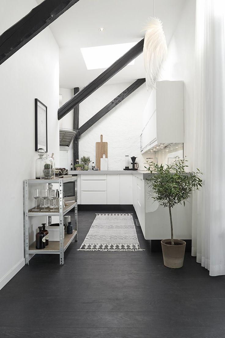Med kun 59 kvadratmeter har denne lejligheden på snedigste vis fået to etager. Et moderne touch i sorte og hvide nuancer spiller sammen med lejlighedens gamle murstensvægge og tværbjælker.