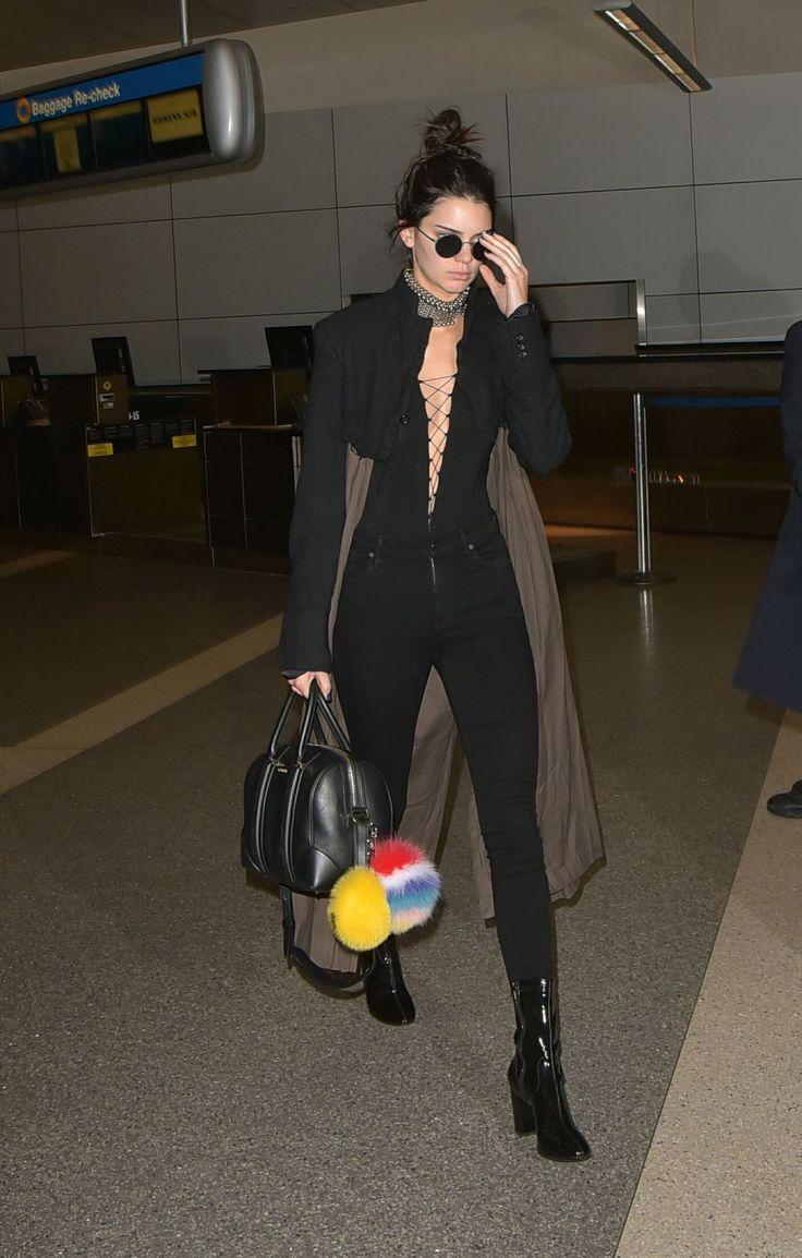 Kendall Jenner airport style, black skinny jeans, trench coat and blouse with Fendi pom poms.