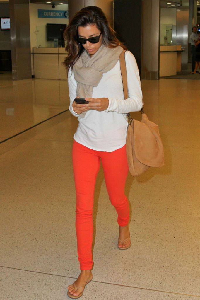 Eva Longoria in coral skinny jeans and a lightweight white sweater, celebrity street style, airport style #EvaLongoria