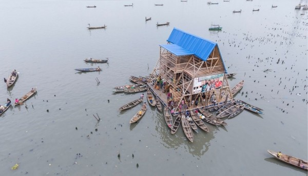 The Makoko Floating School, designed by NLÉ, is located within the floating slums of Lagos. Unlike many of its neighbor structures, the school isn't anchored to the ground. Instead, it rises with the ocean on a layer of plastic drums. Its rooms serve as school as well as a shared community space.