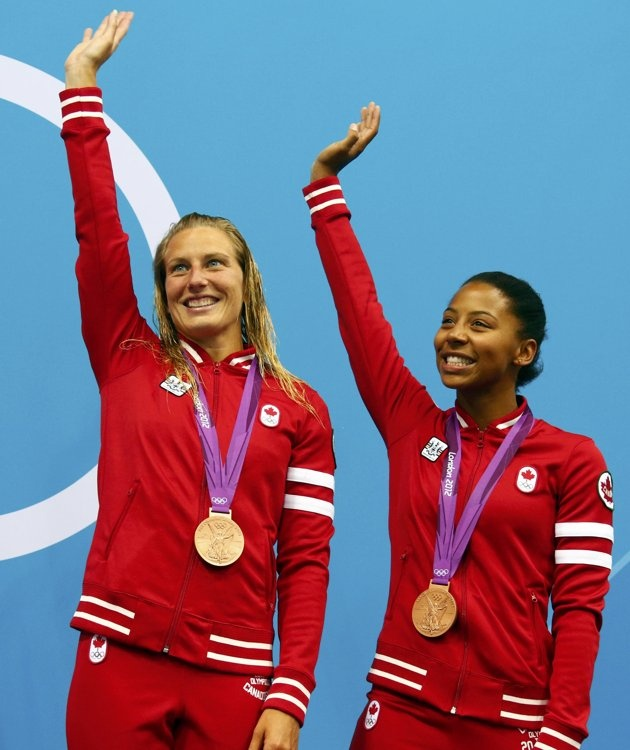 Canada's Jennifer Abel and Emilie Heymans (L) wave after receiving their bronze medals at the women's synchronised 3m springboard victory ceremony during the London 2012 Olympic Games at the Aquatics Centre July 29, 2012.