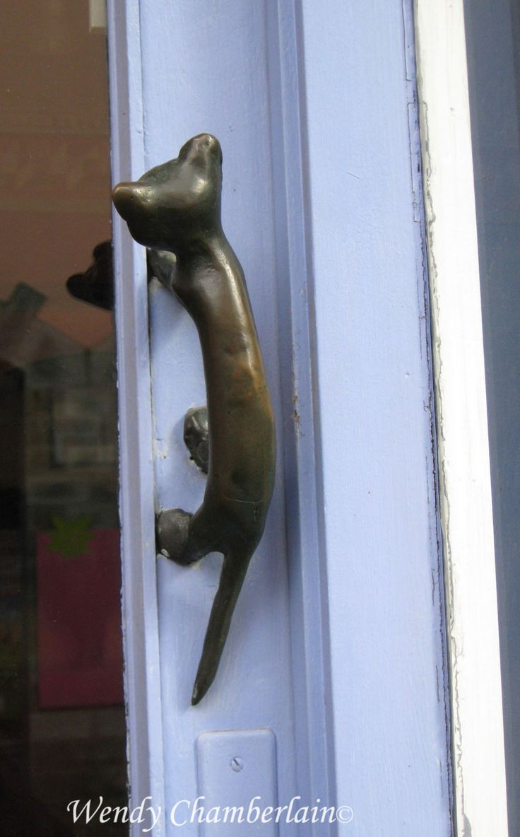 Cat door handle on shop in Brittany