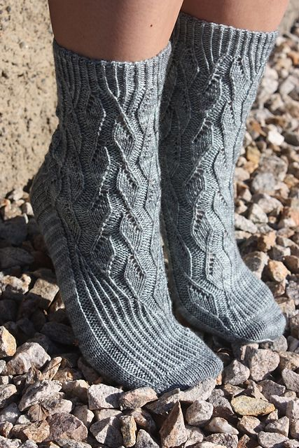 These glamorous cuff-down socks were designed to feature the icy-blue color and subtle sparkle of Ancient Arts Fibre's Fog Warning colorway. The pattern uses twisted ribbing and lace to create intricate and feminine socks. Right and left socks are mirror images.