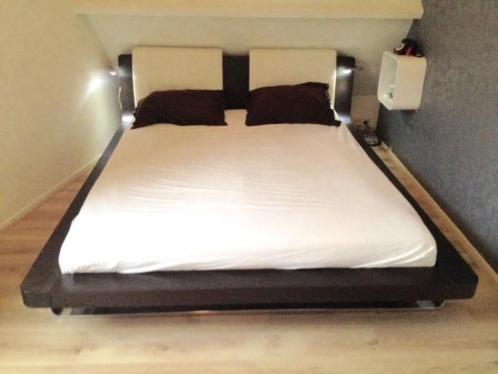 Mooi tijdloos massief hülsta bed, uitgevoerd met twee lednachtlampjes, met beweegbare arm. En twee lederen cremewitte rugsteunen(afneembaar). Inclusief lattenbodem. Matrasmaat 160*200.