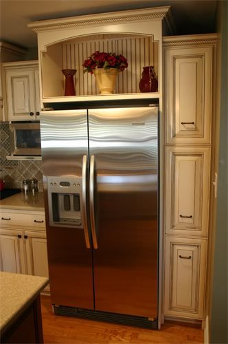 Beadboard panel slides open to reveal a hidden storage area above the refrigerator.