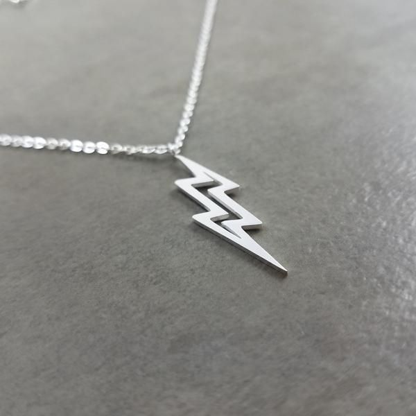 Lightning is a sudden electrostatic discharge that occurs during a thunder storm. This discharge occurs between electrically charged regions of a cloud, between two clouds, or between a cloud and the ground.  Pendant:    Silver plated  1 inch x 1/4 inch (24 mm x 6 mm)    Chain Size:    Silver plated  1 mm in width  17.5 inches in length