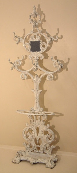 """Antique Victorian Cast Iron Hall Tree. This Victorian """"Hall tree"""" is made from solid cast iron and dates from the late 19th century in America. The casting is quite good obviously done by a very skilled American Victorian period foundry. Victorian cast iron hall trees are difficult to acquire we have only had three in 30 years of selling fine antiques. This hall tree is in excellent condition with one small piece off the umbrella tray on the base. Repainted several years ago in white. This…"""
